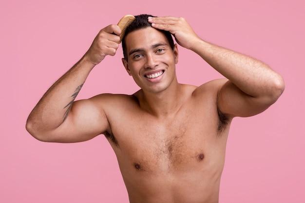 Vista frontal de um homem sorridente penteando o cabelo