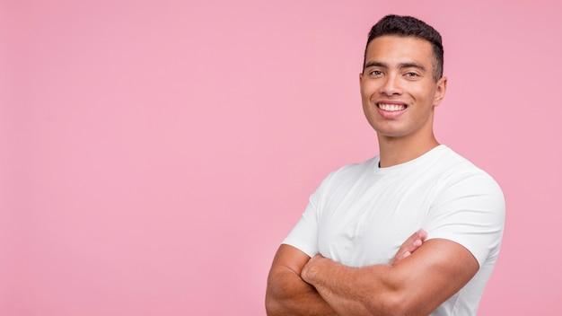 Vista frontal de um homem sorridente posando com os braços cruzados