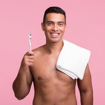 Vista frontal de um homem sorridente segurando uma escova de dentes e uma toalha