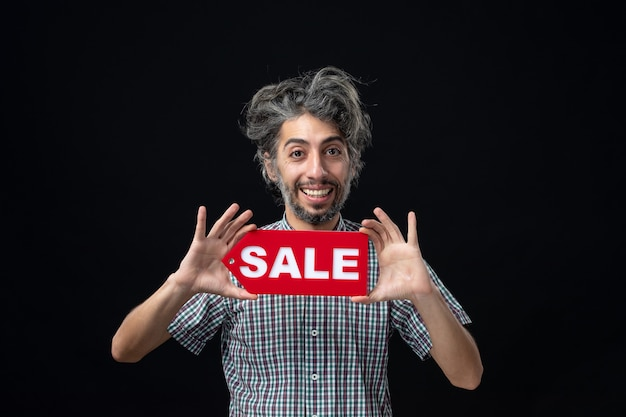 Vista frontal de um homem sorridente segurando uma placa de venda na parede escura