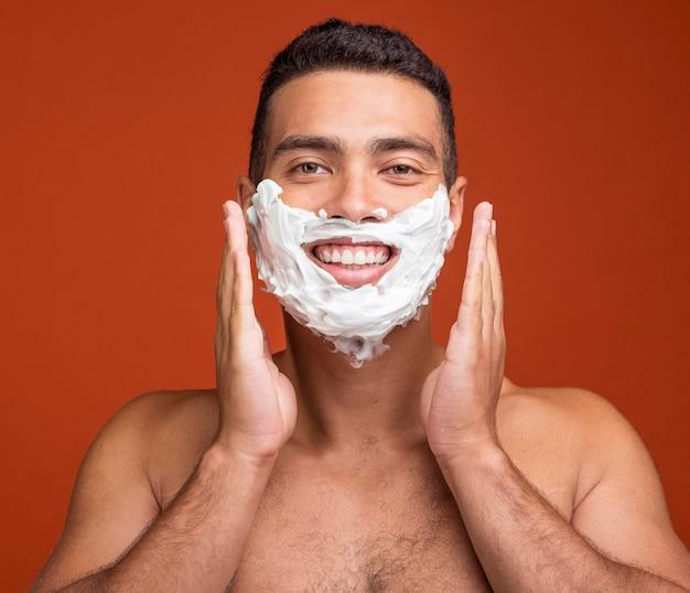 Vista frontal de um homem sorridente sem camisa com espuma de barbear no rosto