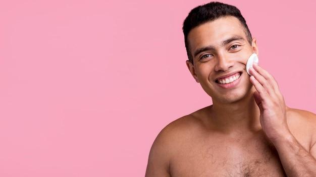Vista frontal de um homem sorridente sem camisa usando almofadas de algodão no rosto