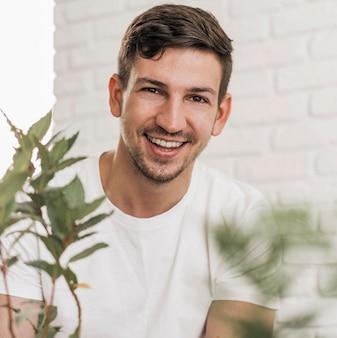Vista frontal de um homem sorridente sentado ao lado de plantas