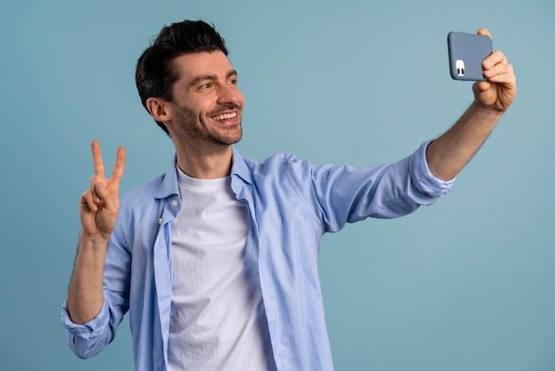 Vista frontal de um homem sorridente tirando uma selfie com o smartphone
