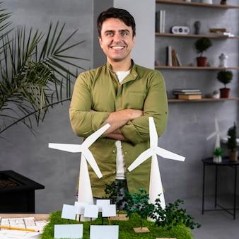 Vista frontal de um homem sorridente trabalhando em um projeto de energia eólica ecologicamente correto com turbinas eólicas
