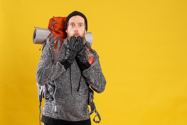 Vista frontal de um homem surpreso, caroneiro com luvas de couro e mochila