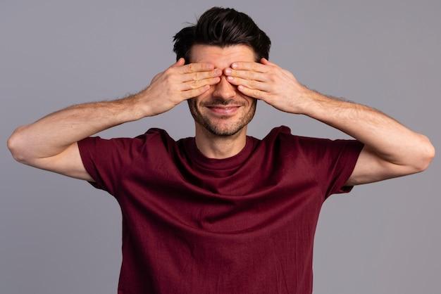 Vista frontal de um homem tímido cobrindo os olhos com as mãos