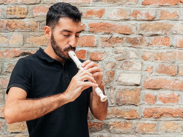 Vista frontal de um homem tocando flauta