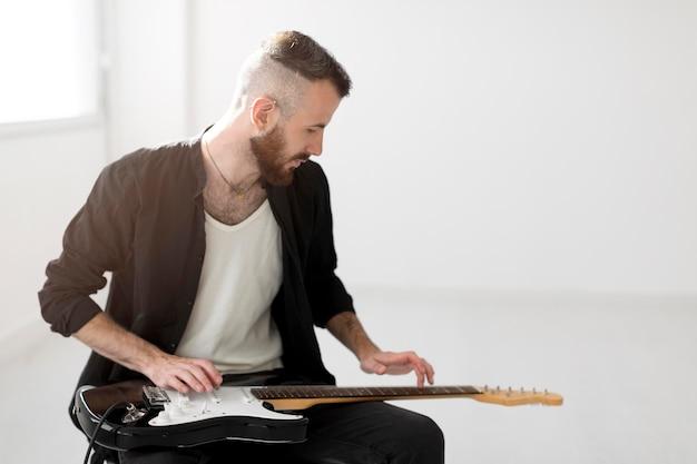 Vista frontal de um homem tocando guitarra elétrica