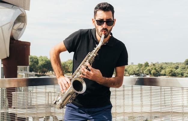 Vista frontal de um homem tocando saxofone