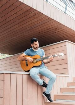 Vista frontal de um homem tocando violão