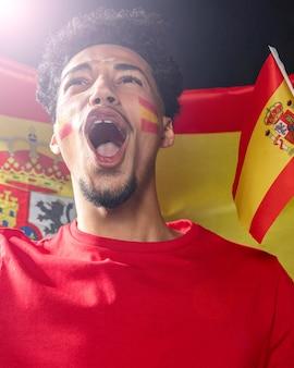 Vista frontal de um homem torcendo e segurando a bandeira da espanha