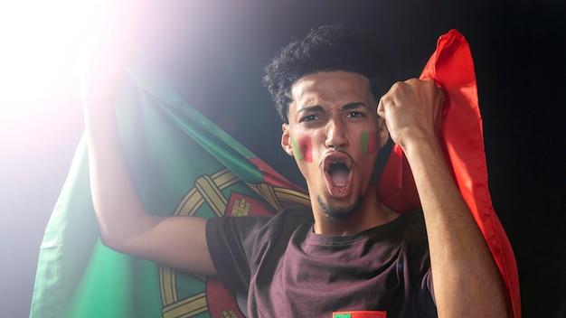 Vista frontal de um homem torcendo e segurando a bandeira de portugal
