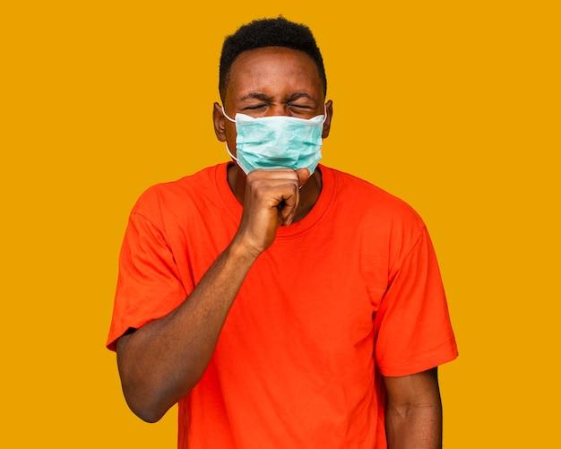 Vista frontal de um homem tossindo com máscara facial