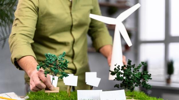 Vista frontal de um homem trabalhando em um layout de projeto de energia eólica ecologicamente correto
