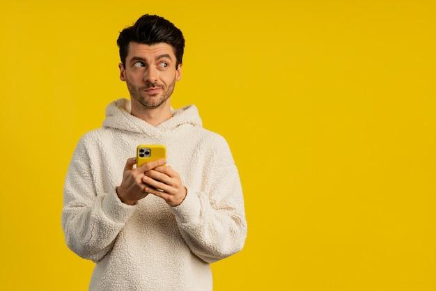 Vista frontal de um homem travesso enquanto segura um smartphone