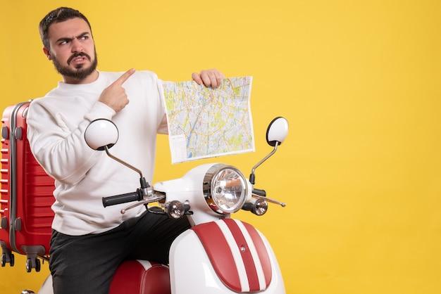 Vista frontal de um homem zangado sentado em uma motocicleta com uma mala segurando um mapa apontando para cima em um fundo amarelo isolado