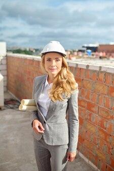 Vista frontal de um inspetor de construção calmo com desenhos técnicos enrolados debaixo do braço em pé no canteiro de obras