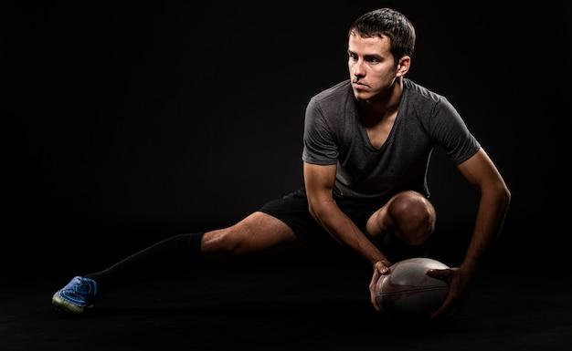 Vista frontal de um jogador de rúgbi atlético segurando uma bola