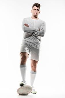 Vista frontal de um jogador de rúgbi posando com a bola e os braços cruzados