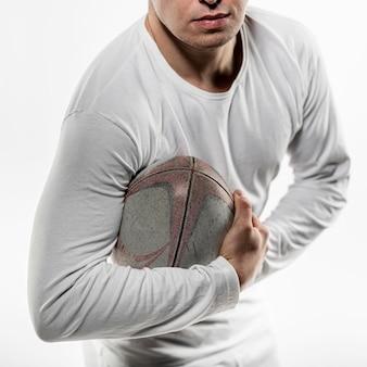 Vista frontal de um jogador de rúgbi posando segurando uma bola