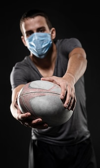 Vista frontal de um jogador de rugby com máscara médica segurando uma bola