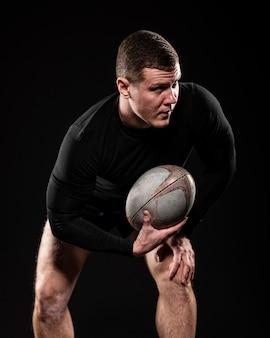 Vista frontal de um jogador de rugby segurando uma bola com uma das mãos