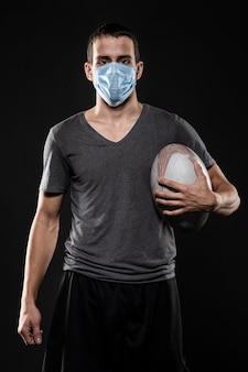 Vista frontal de um jogador de rugby segurando uma bola enquanto usa máscara médica