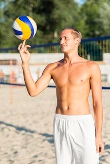 Vista frontal de um jogador de vôlei masculino sem camisa fazendo manobras com a bola na praia
