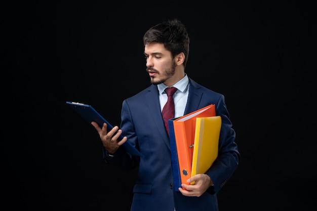 Vista frontal de um jovem adulto concentrado em um terno segurando vários documentos em uma parede escura isolada