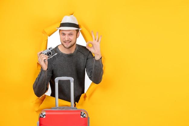 Vista frontal de um jovem adulto confiante segurando uma sacola e fazendo um gesto de óculos em uma parede amarela rasgada