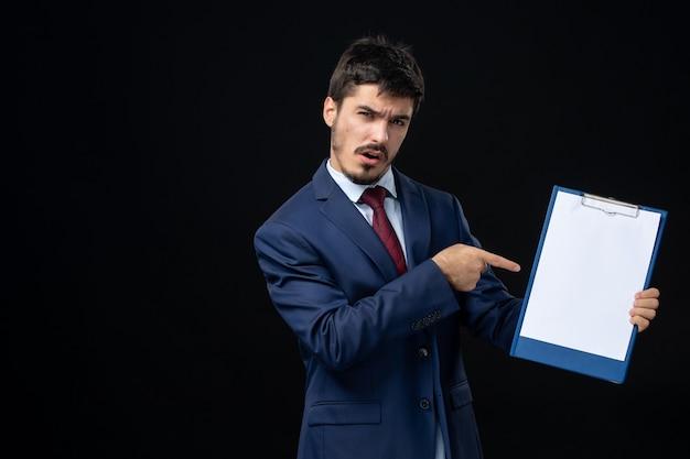 Vista frontal de um jovem adulto confuso em um terno mostrando espaço livre para escrever na parede escura isolada