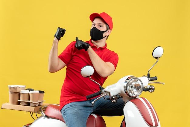Vista frontal de um jovem adulto curioso usando uma blusa vermelha e luvas de chapéu na máscara médica, entregando o pedido sentado na scooter, apontando para trás no fundo amarelo