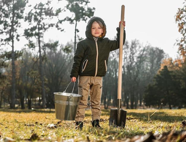Vista frontal de um jovem ao ar livre segurando um balde e uma pá
