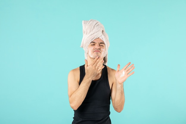 Vista frontal de um jovem após o banho, aplicando creme em seu rosto na parede azul
