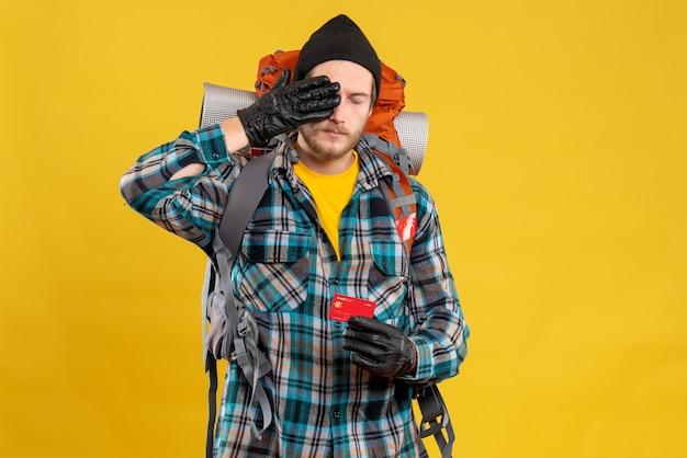 Vista frontal de um jovem barbudo com mochileiro e cartão de crédito segurando seu olho