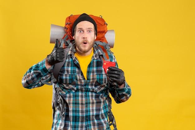 Vista frontal de um jovem barbudo com um mochileiro segurando um cartão de crédito e desistindo do polegar
