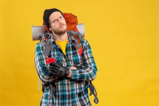 Vista frontal de um jovem barbudo com um mochileiro segurando um cartão de desconto cruzando as mãos