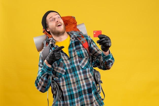 Vista frontal de um jovem barbudo com um mochileiro segurando um cartão de descontos