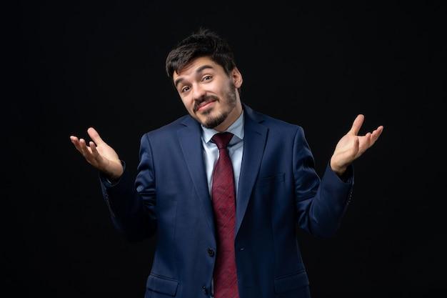 Vista frontal de um jovem barbudo em um terno posando com uma expressão facial suspeita em uma parede escura isolada