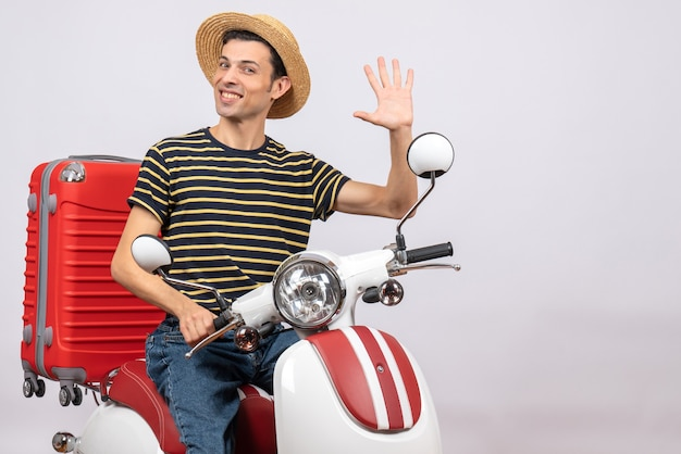 Vista frontal de um jovem bonito com chapéu de palha na motocicleta acenando com a mão