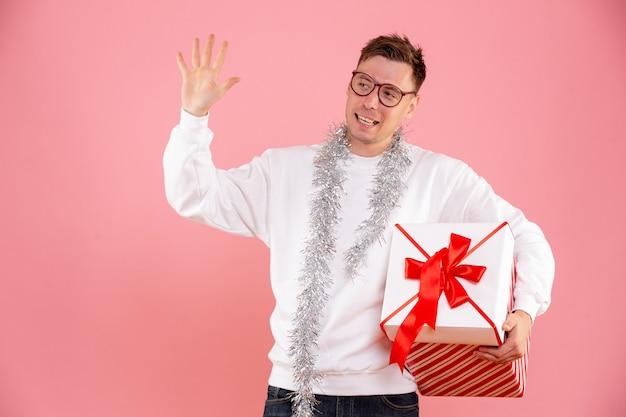 Vista frontal de um jovem carregando o presente de natal na parede rosa