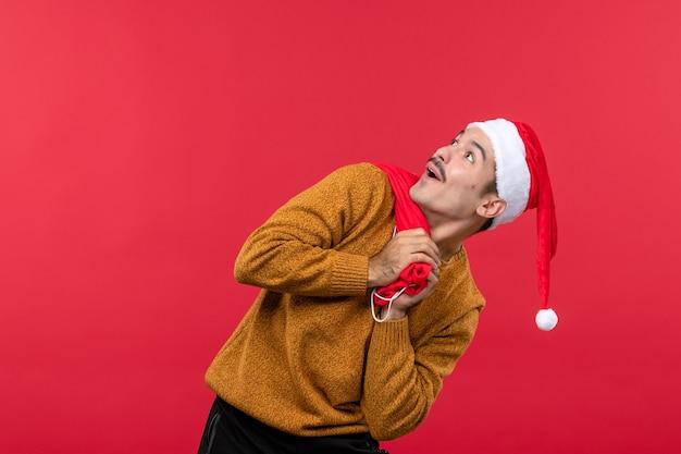 Vista frontal de um jovem carregando uma sacola de presentes na parede vermelha