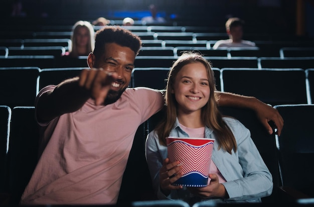 Vista frontal de um jovem casal alegre no cinema, apontando para a câmera.