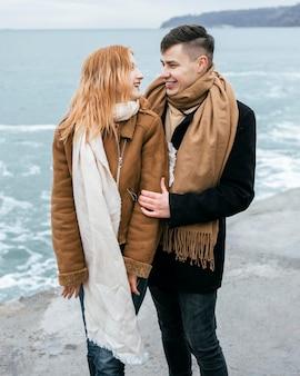 Vista frontal de um jovem casal na praia no inverno