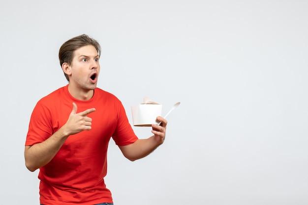 Vista frontal de um jovem chocado com uma blusa vermelha apontando para uma caixa de papel no fundo branco