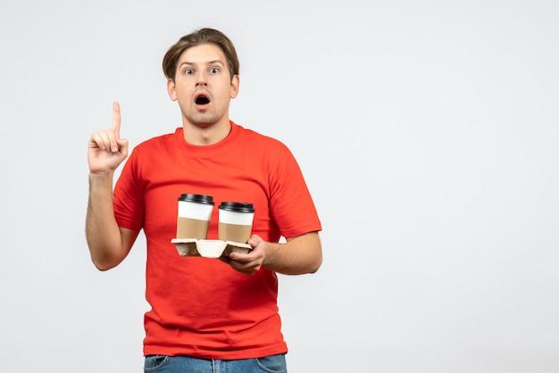 Vista frontal de um jovem chocado com uma blusa vermelha segurando café em copos de papel e apontando para cima no fundo branco