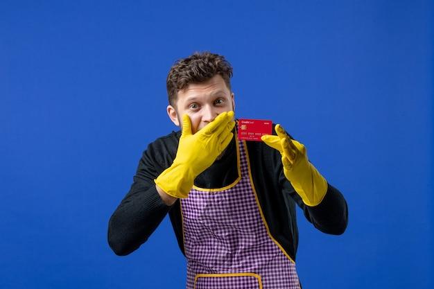 Vista frontal de um jovem colocando a mão no rosto, segurando o cartão na mão esquerda na parede azul
