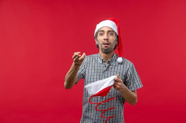 Vista frontal de um jovem com boné de brinquedo de natal na parede vermelha
