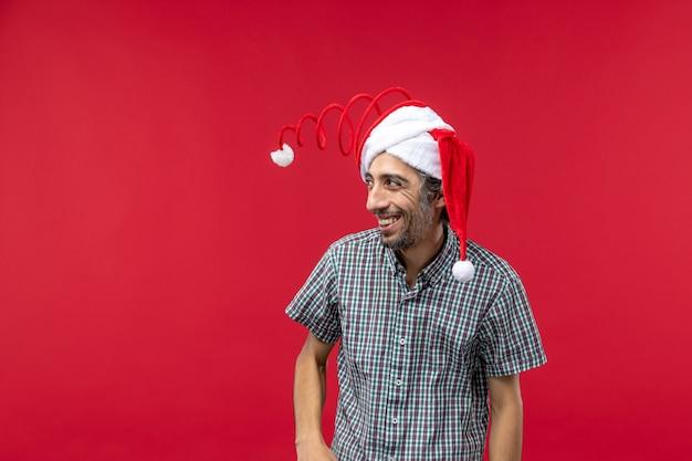 Vista frontal de um jovem com boné de brinquedo engraçado na parede vermelha